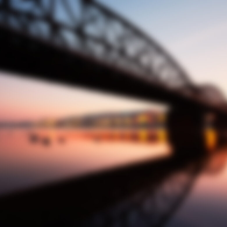 Amazing sunrise in the city. Railway bridge (with reflection in the river) and embankment in Prague, Czech Republic.